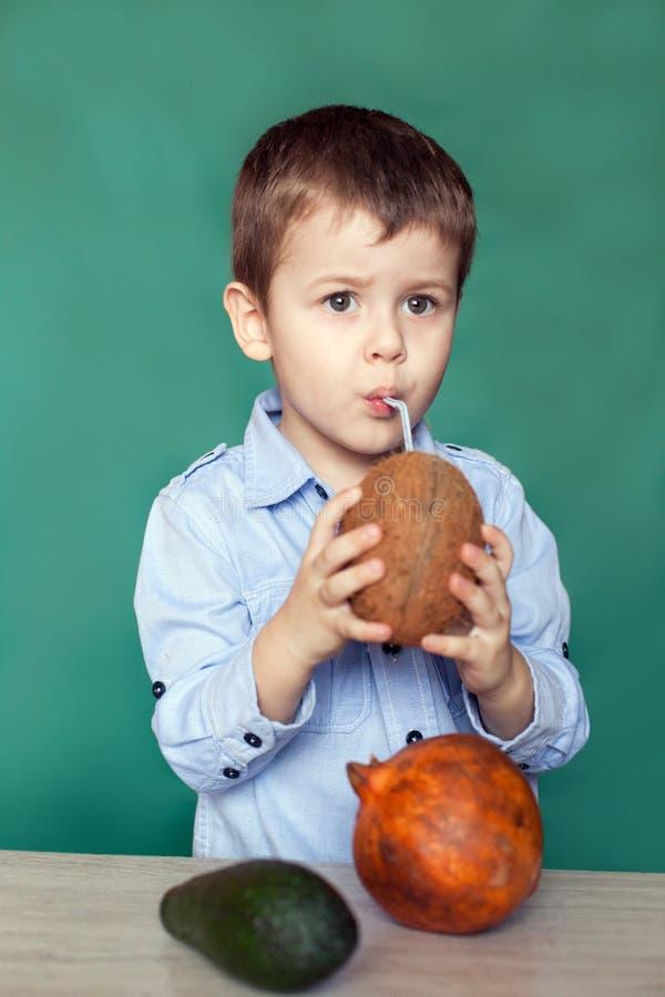 Leuk weinig jongen het drinken kokosnotencocktail op groene achtergrond royalty-vrije stock foto's