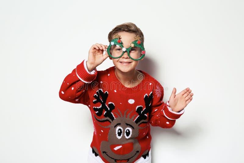 Leuk weinig jongen in Kerstmissweater met partijglazen stock afbeeldingen