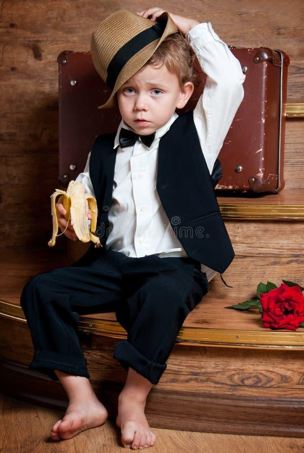 Leuk weinig jongen met een banaan. stock afbeelding