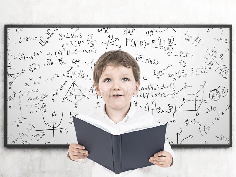 Leuk weinig jongen met een boek, formule stock afbeeldingen