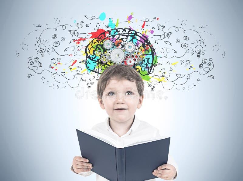 Leuk weinig jongen met een boek, radertjehersenen stock foto