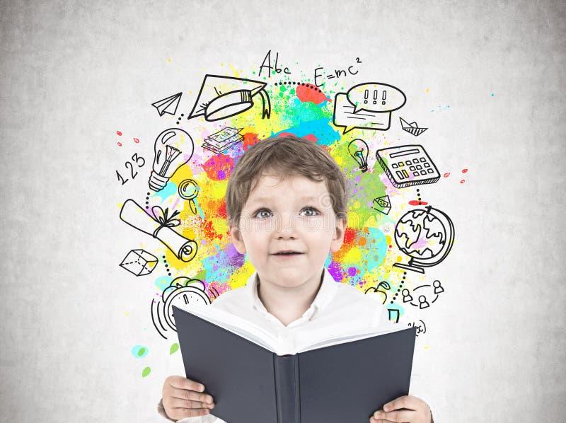 Leuk weinig jongen met een boek, school stock fotografie