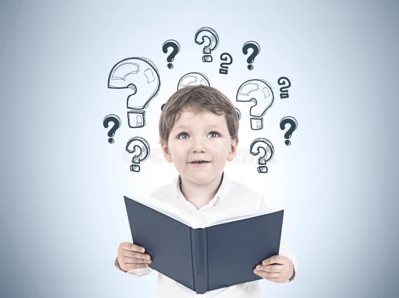 Leuk weinig jongen met een boek, vraagtekens stock foto's