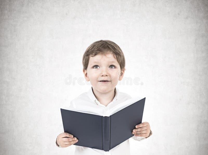 Leuk weinig jongen met een concreet boek, royalty-vrije stock fotografie