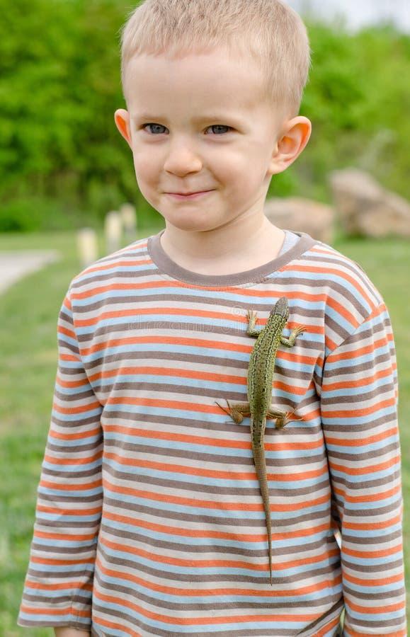 Leuk weinig jongen met een levende hagedis op zijn overhemd royalty-vrije stock afbeeldingen
