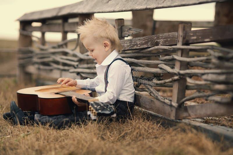 Leuk weinig jongen met gitaar stock afbeelding
