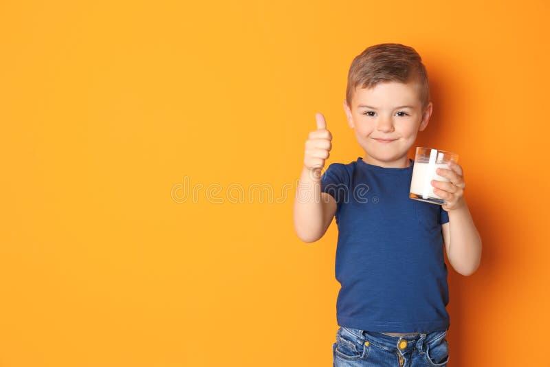Leuk weinig jongen met glas melk op kleurenachtergrond royalty-vrije stock afbeelding