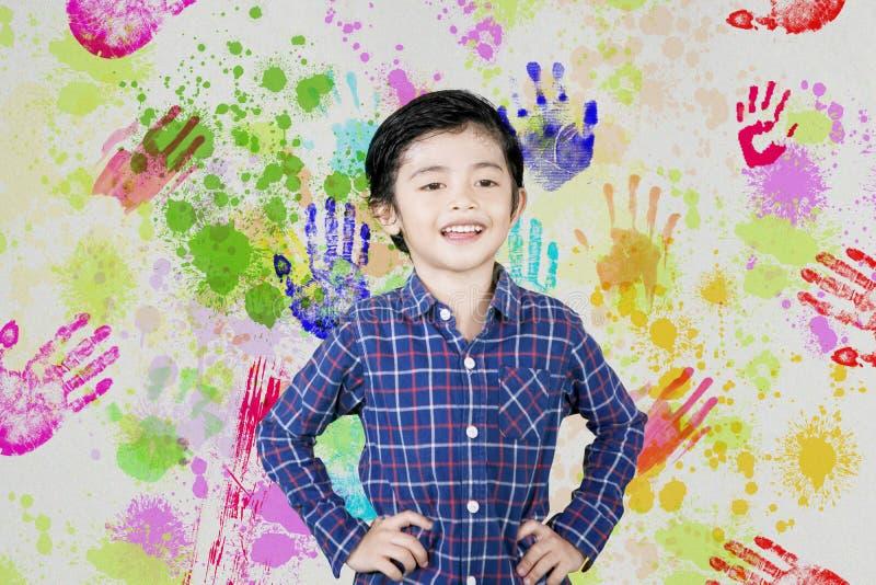 Leuk weinig jongen met kleurrijke drukken van handen stock foto