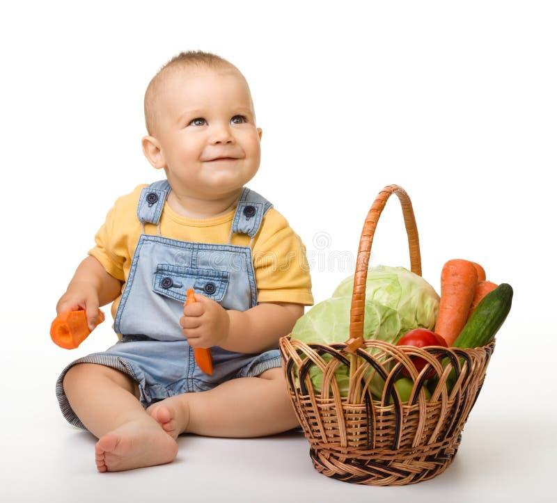 Leuk weinig jongen met mandhoogtepunt van groenten stock fotografie