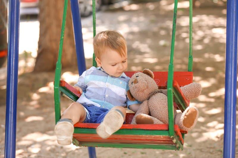 Leuk weinig jongen met teddybeer het spelen op schommeling in openlucht stock foto's