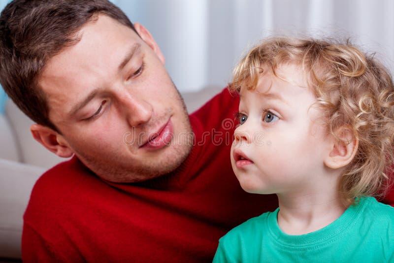 Leuk weinig jongen met zijn papa stock afbeelding