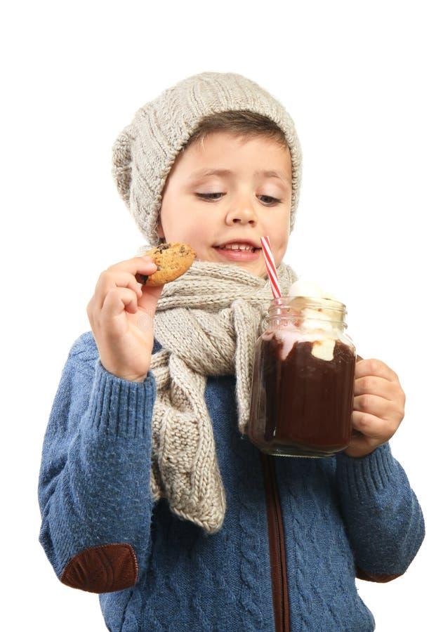 Leuk weinig jongen in warme kleren met metselaarkruik van heet chocolade en koekje op witte achtergrond stock afbeeldingen
