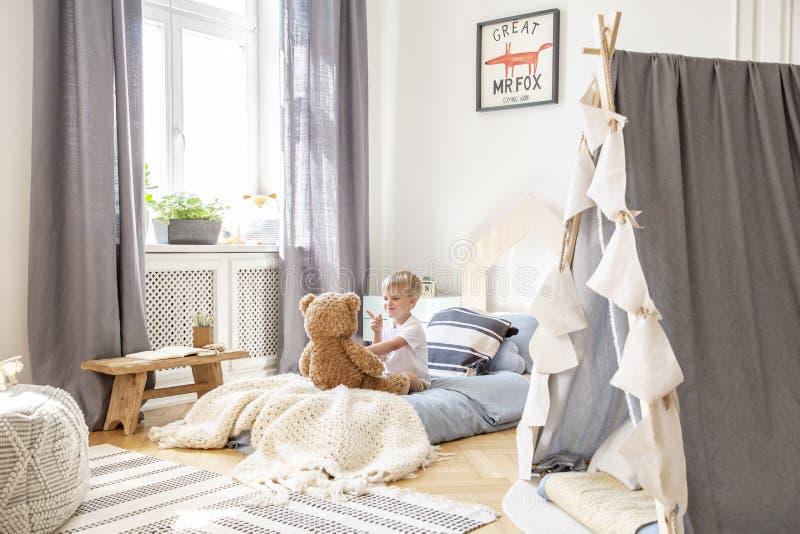 Leuk weinig jongenszitting in het comfortabele bed spelen met teddybeer, echte foto van natuurlijk speelkamerbinnenland royalty-vrije stock afbeeldingen