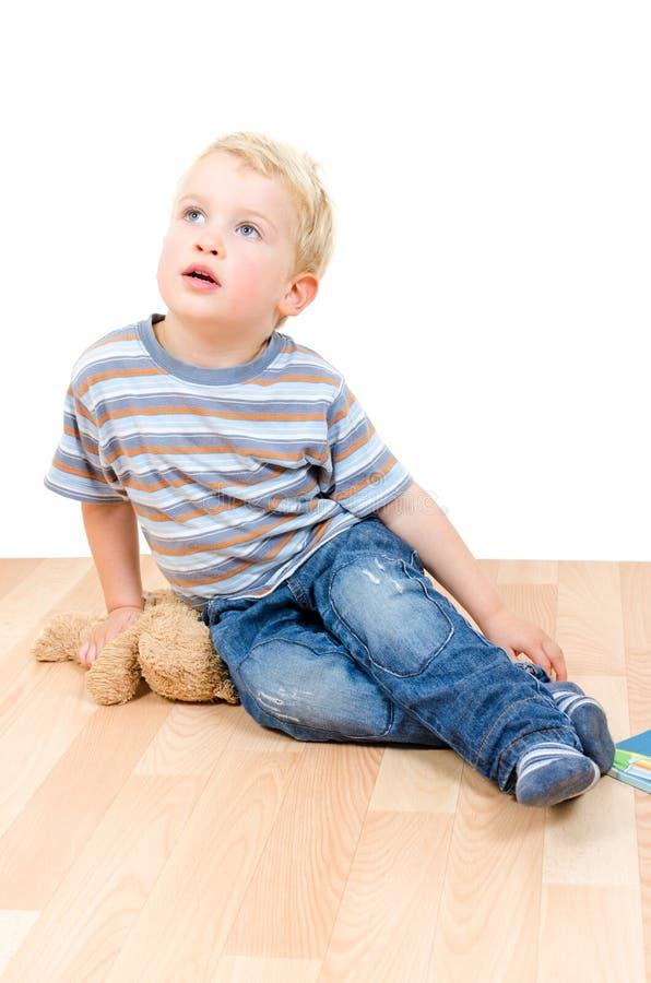 Leuk weinig jongenszitting met geïsoleerde teddybeer en boek royalty-vrije stock afbeelding