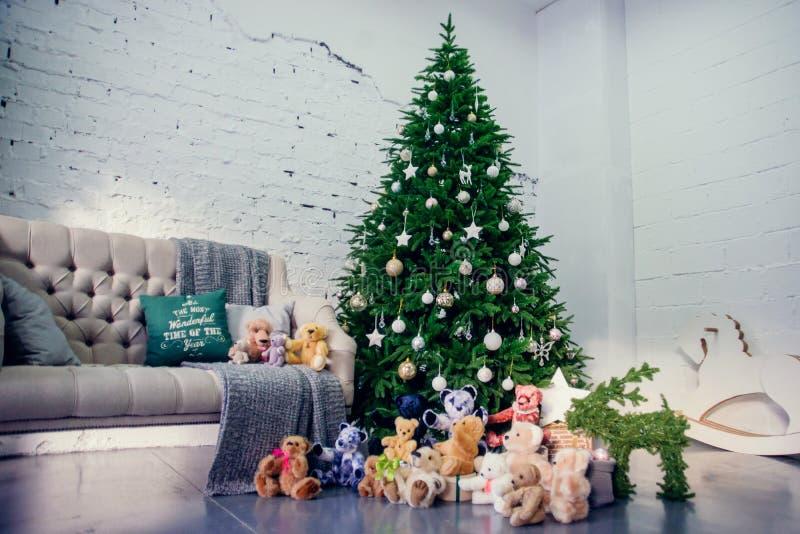 Leuk weinig jongenszitting neer door de verfraaide Kerstboom met speelgoed, teddyberen en giftdozen royalty-vrije stock fotografie