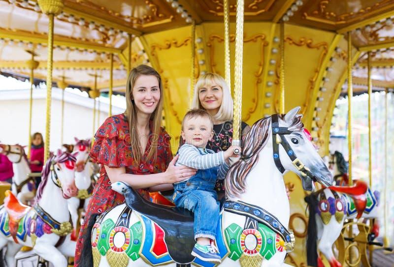 Leuk weinig jongenszitting op carrouselpaard stock afbeeldingen