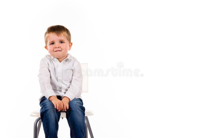 Leuk weinig jongenszitting op een kruk stock foto