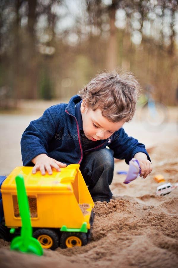 Leuk weinig jongenszitting op het zand en het spelen in een stuk speelgoed auto Park op de achtergrond Verticale foto royalty-vrije stock foto
