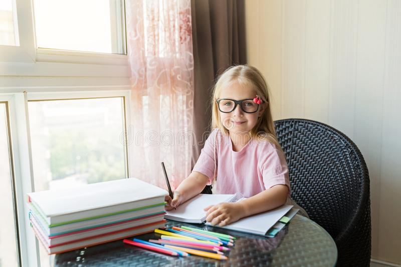 Leuk weinig Kaukasisch meisje die thuiswerk doen en een document schrijven Het jonge geitje geniet van thuis lerend met geluk Sli stock foto's