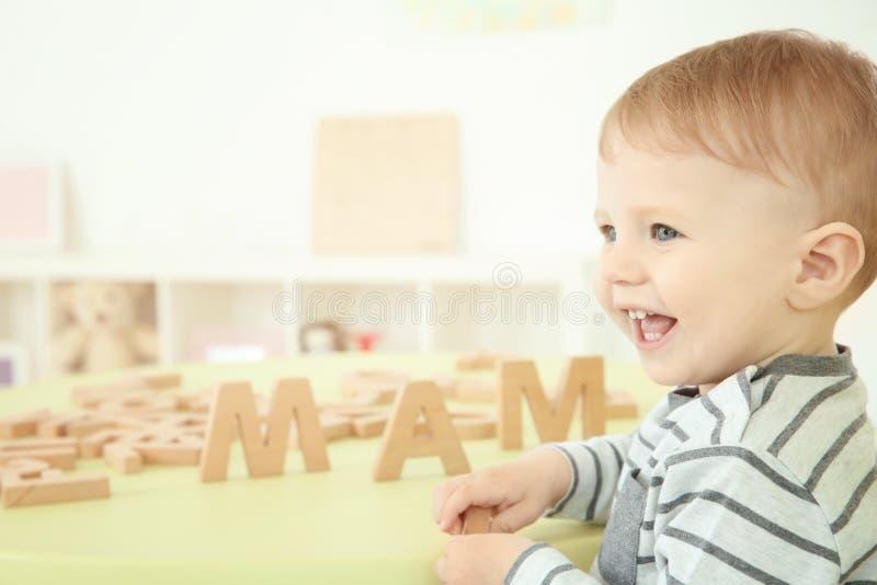 Leuk weinig kind die met brieven spelen stock afbeelding