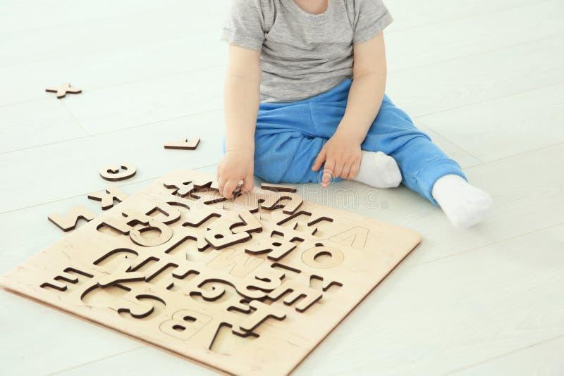 Leuk weinig kind die met brieven spelen terwijl het zitten op vloer stock fotografie