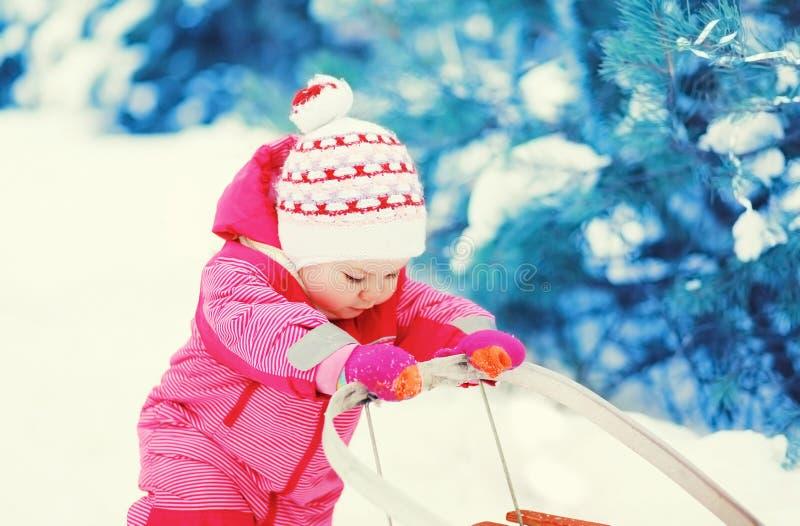 Leuk weinig kind die met slee op sneeuw in de winter spelen royalty-vrije stock foto's