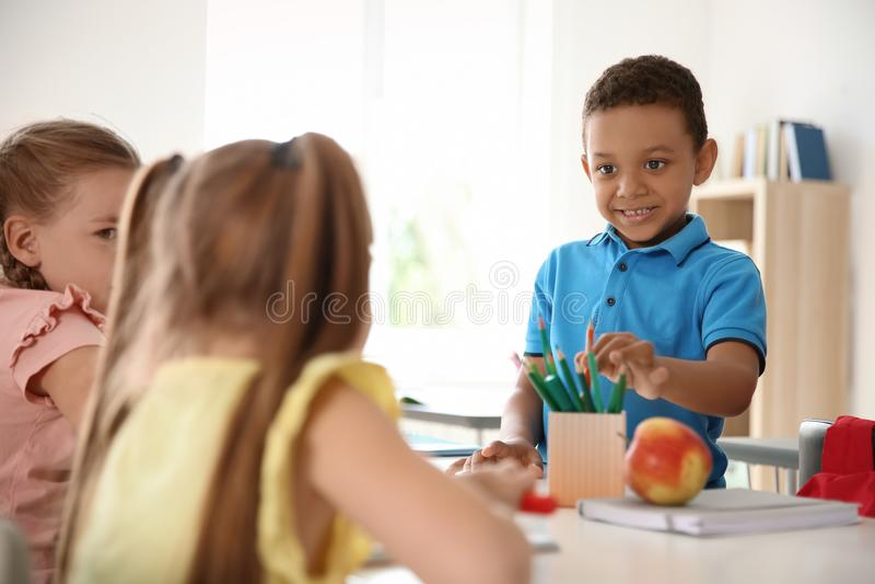 Leuk weinig kind die zijn klasgenoot` s potlood nemen stock fotografie