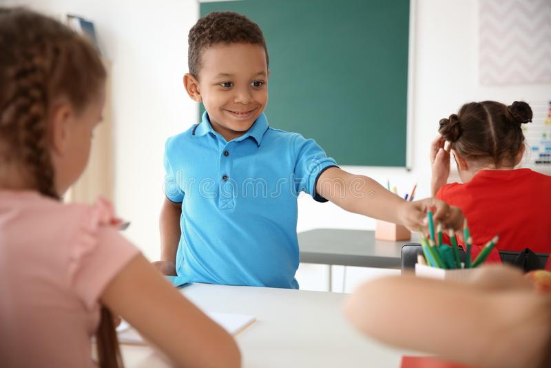Leuk weinig kind die zijn klasgenoot` s potlood nemen stock afbeelding