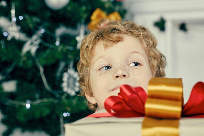 Leuk weinig kindjongen die achter een grote giftdoos verbergen Het jonge geitje houdt een giftdoos binnen dichtbij Kerstboom stock fotografie