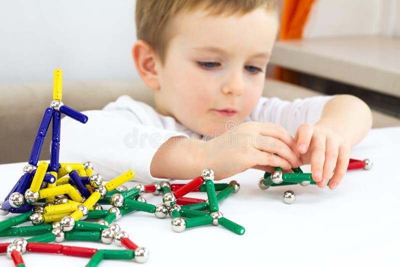 Leuk weinig kindjongen het spelen magnetenstuk speelgoed voor hersenenontwikkeling, fijn motorvaardigheden en creativiteitconcept stock afbeeldingen