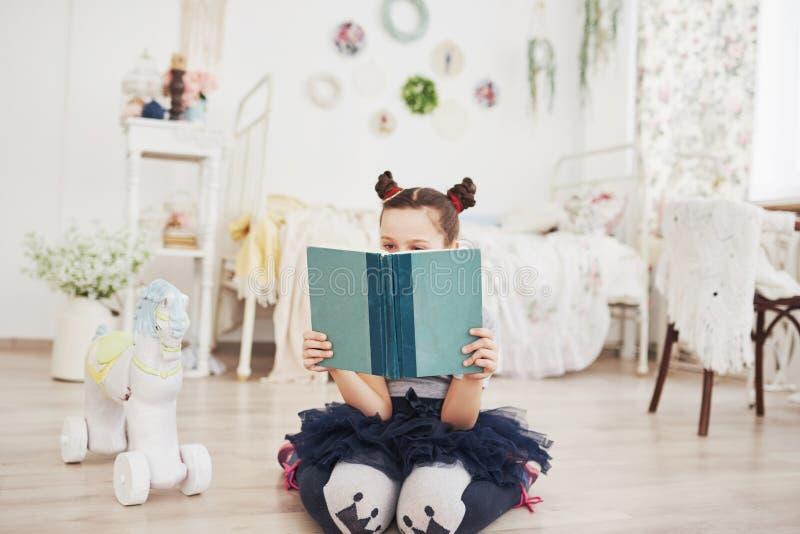 Leuk weinig kindmeisje die een boek in de slaapkamer lezen Jong geitje met kroonzitting op het bed dichtbij venster royalty-vrije stock foto