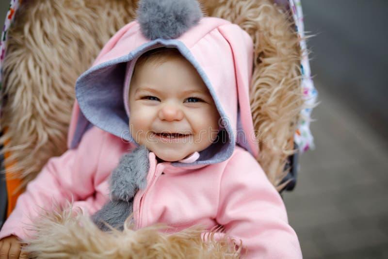 Leuk weinig mooie zitting van het babymeisje in de kinderwagen of de wandelwagen op de herfstdag Gelukkig glimlachend kind in war royalty-vrije stock foto's