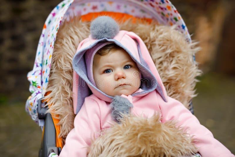 Leuk weinig mooie zitting van het babymeisje in de kinderwagen of de wandelwagen op de herfstdag Gelukkig glimlachend kind in war stock afbeeldingen