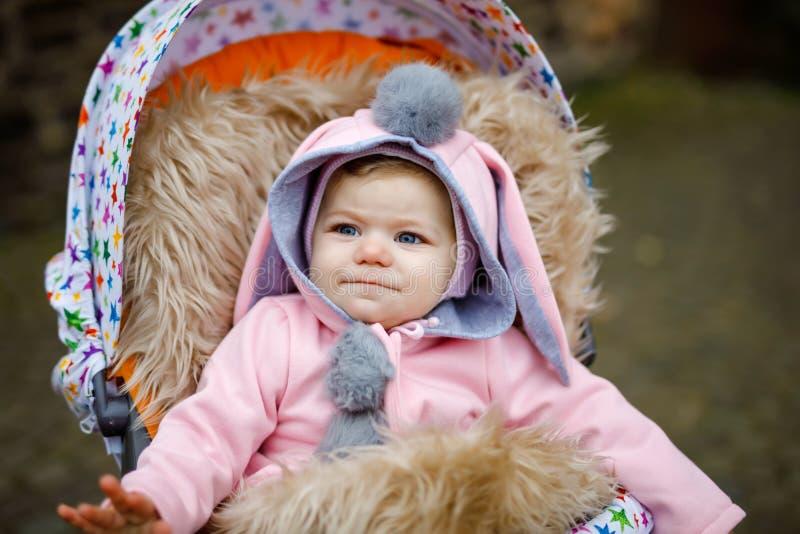 Leuk weinig mooie zitting van het babymeisje in de kinderwagen of de wandelwagen op de herfstdag Gelukkig glimlachend kind in war royalty-vrije stock afbeelding