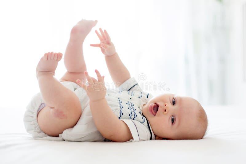 Leuk weinig oude babyjongen van vier maanden, die thuis in bed spelen royalty-vrije stock foto
