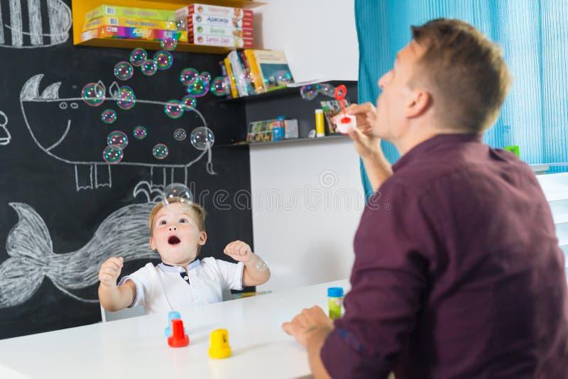 Leuk weinig peuterjongen bij speechtherapistzitting stock afbeeldingen