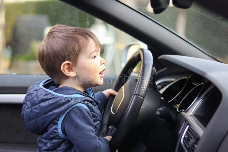 Leuk weinig peuterjongen die het grote stuurwiel drijven die van de autoholding vooruit windscherm bekijken stock foto's