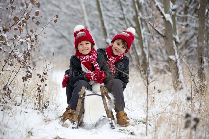 Leuk weinig peuterjongen en zijn oudere broers, die in openlucht met sneeuw op een de winterdag spelen royalty-vrije stock afbeeldingen