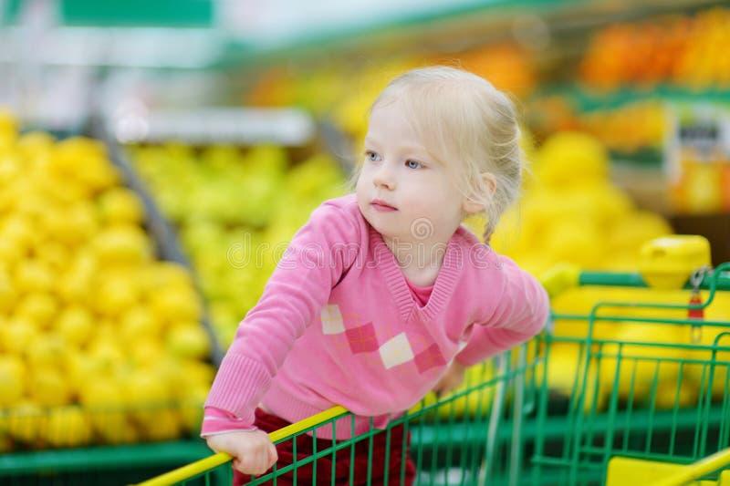 Leuk weinig peutermeisje die in een voedselopslag winkelen royalty-vrije stock afbeeldingen