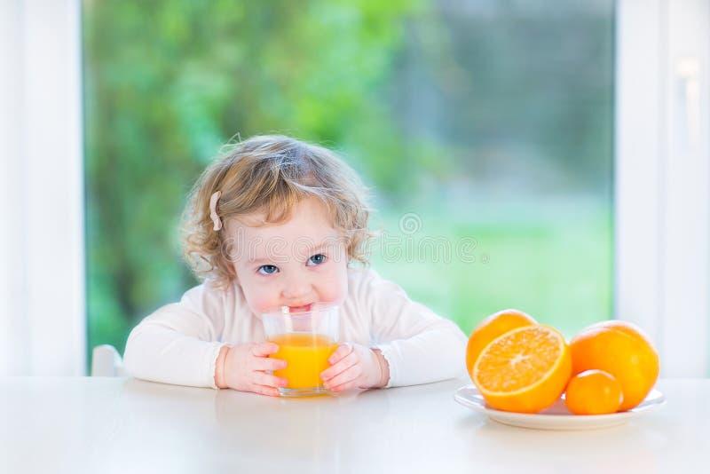 Leuk weinig peutermeisje het drinken jus d'orange stock foto's