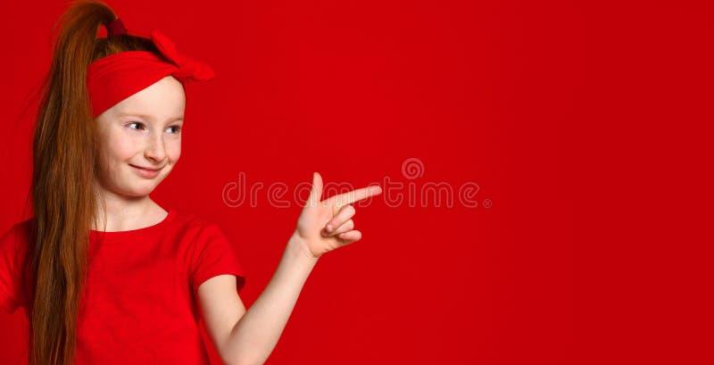 Leuk weinig roodharig meisje met een verband op haar haar, glimlachen en plaatsen een vlek voor uw reclame stock fotografie