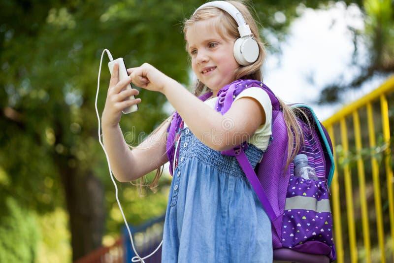 Leuk weinig school-girl die aan muziek buiten met wit luisteren hij royalty-vrije stock afbeelding