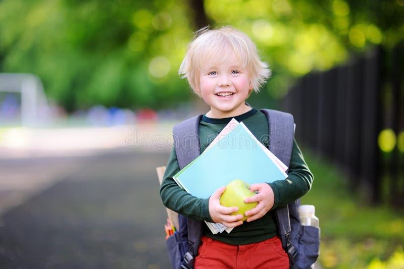 Leuk weinig schooljongen met zijn rugzak en appel Terug naar het Concept van de School stock foto
