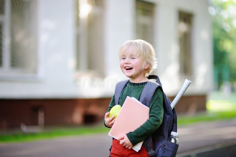 Leuk weinig schooljongen met zijn rugzak en appel Terug naar het Concept van de School stock afbeeldingen
