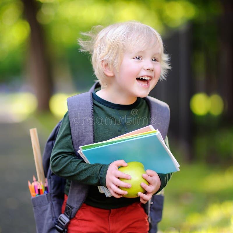 Leuk weinig schooljongen met zijn rugzak en appel Terug naar schoo stock fotografie