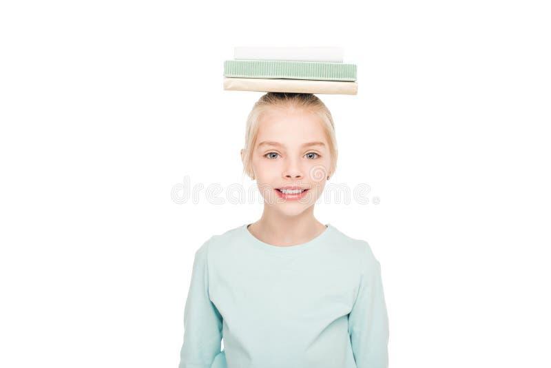 leuk weinig schoolmeisje die met boeken op hoofd bij camera glimlachen stock foto's