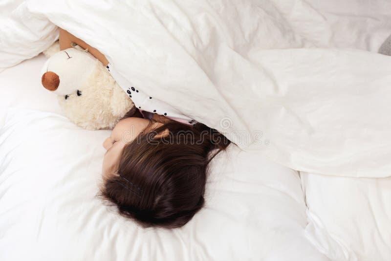 Leuk weinig slaap van het kindmeisje met teddybeer stock foto