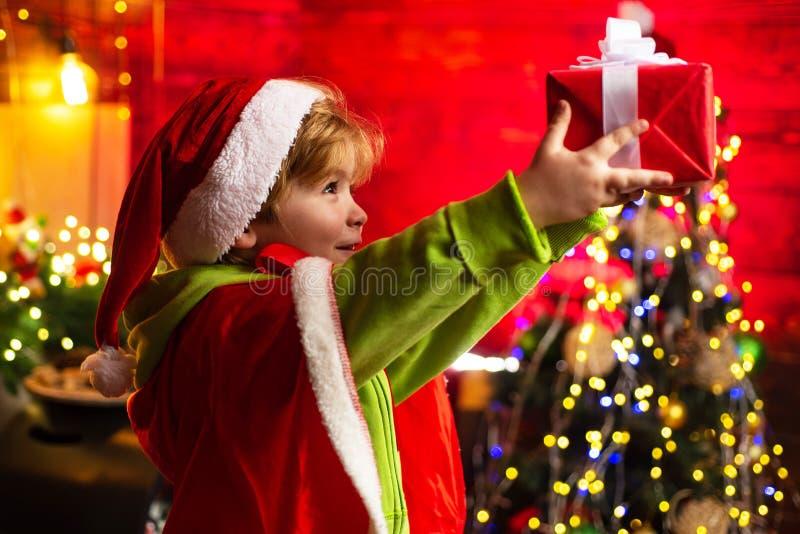Leuk weinig spel van de kindjongen dichtbij Kerstmisboom Het jonge geitje geniet thuis de winter van vakantie Huis met vreugde en stock afbeelding
