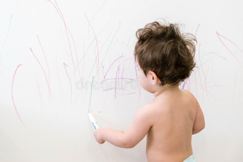 Leuk weinig tekening van de babyjongen met kleurpotloodkleur op de muur De werken van kind De werken van kind Kaukasisch donkerbr royalty-vrije stock afbeeldingen