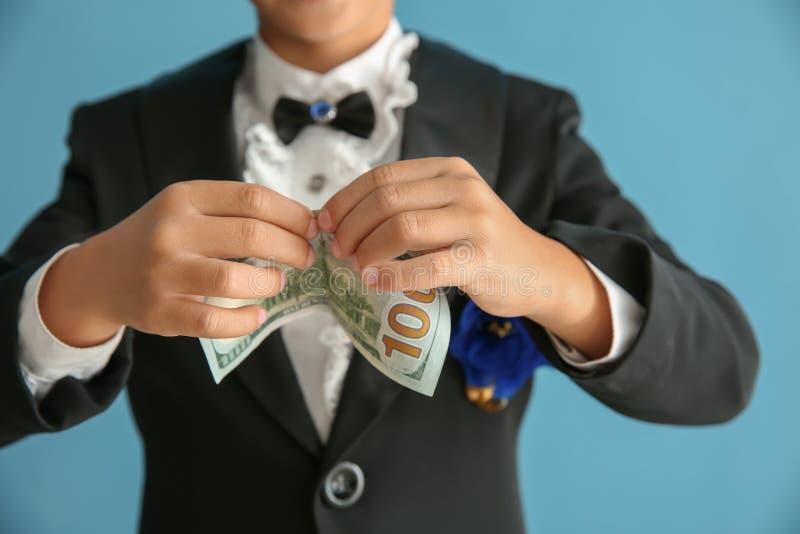 Leuk weinig tovenaar die truc met geld op kleurenachtergrond tonen, close-up stock afbeelding
